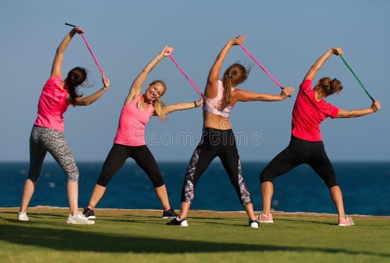做他们的健身训练的小组年轻人由海 免版税库存图片