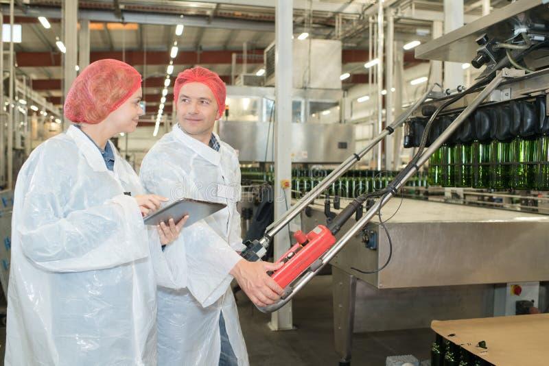 做他们的在工厂生产的两名严肃的体力工人工作 库存图片