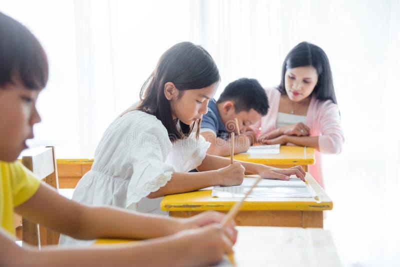 做他们的家庭作业的学生在学校 免版税图库摄影
