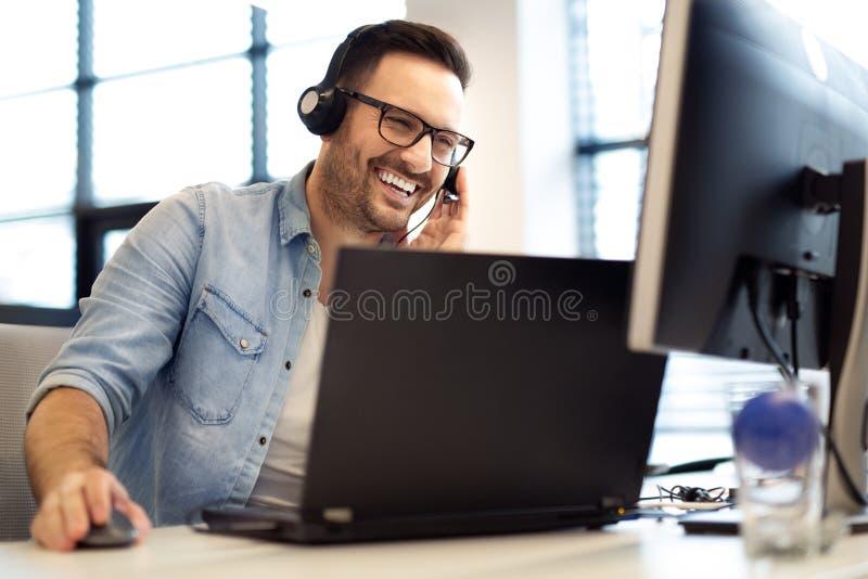 做他的与耳机的年轻微笑的男性电话中心操作员工作 电话中心工作者画象在办公室 库存照片