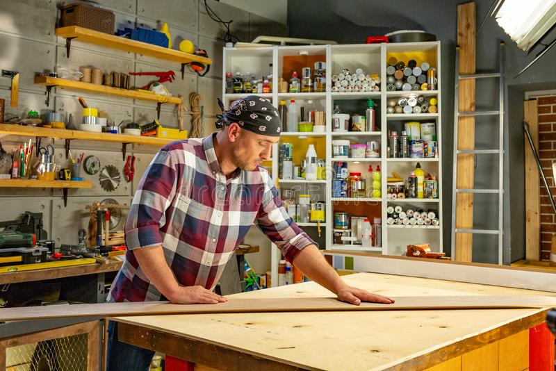 做他的工作的木匠在木匠业车间 木匠业车间测量和裁减层压制品的一个人 免版税库存照片