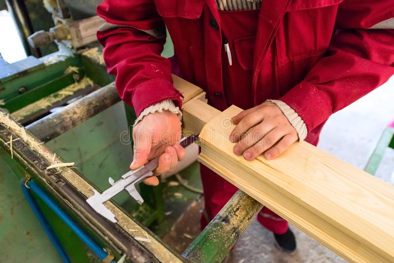 做他的工作的木匠在生产的工厂胶合了timb 免版税图库摄影