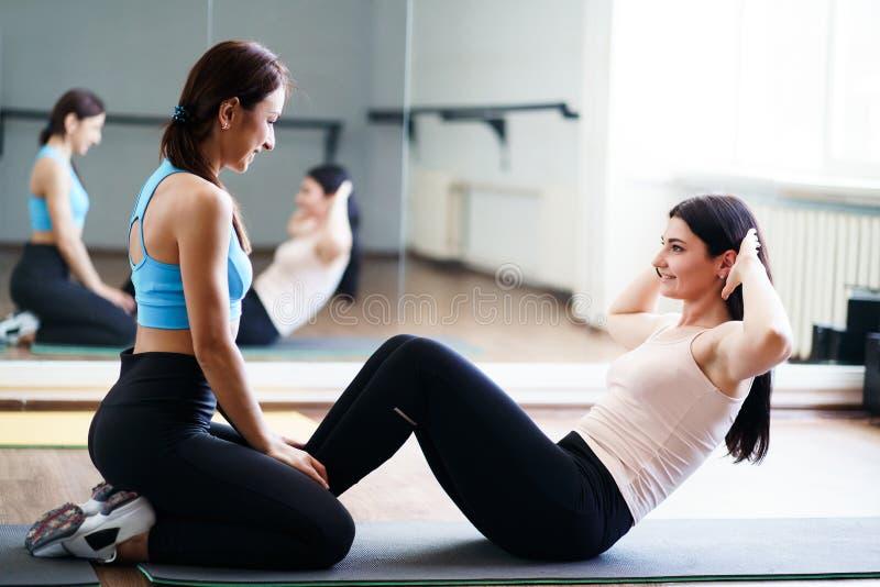 做仰卧起坐有健身辅导员支持的妇女 库存照片