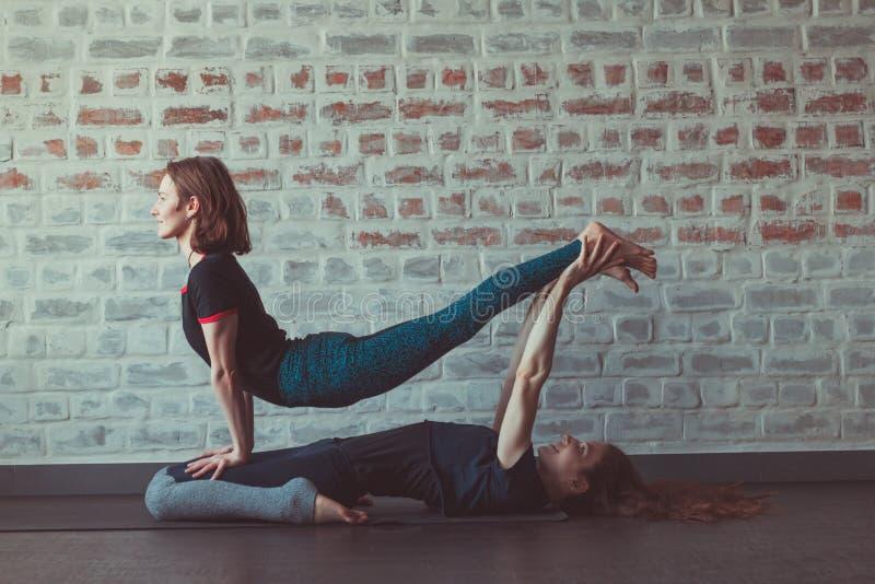 做伙伴瑜伽的两美女在砖墙对面的瑜伽演播室 图库摄影
