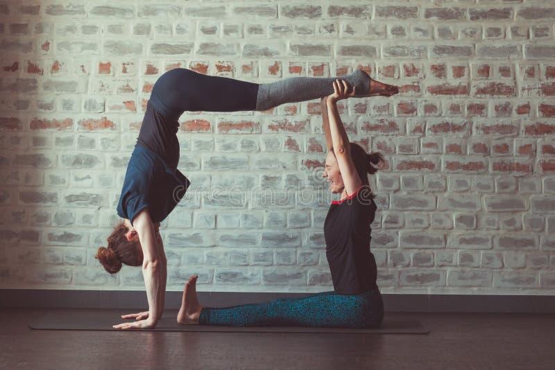 做伙伴瑜伽的两美女在砖墙对面的瑜伽演播室 库存图片