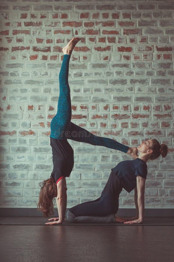 做伙伴瑜伽的两美女在砖墙对面的瑜伽演播室 免版税库存图片