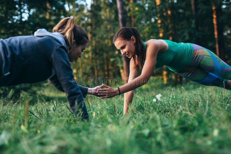 做伙计锻炼的两个女孩户外进行俯卧撑拍手在草 库存图片