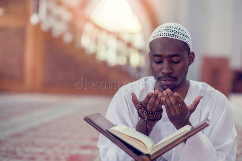 做传统祷告的非洲回教人顶面viewv对上帝,当戴着一个传统帽子Dishdasha时 免版税库存照片