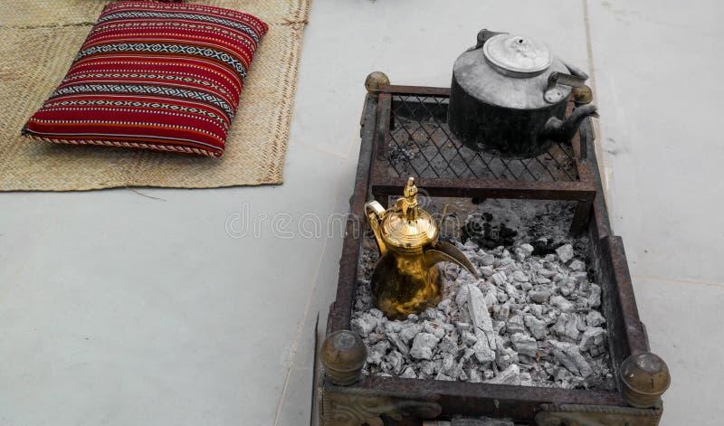 做传统阿拉伯咖啡-金黄阿拉伯语和中东咖啡罐在木炭顶部的Dallah在阿拉伯decorati附近 库存图片