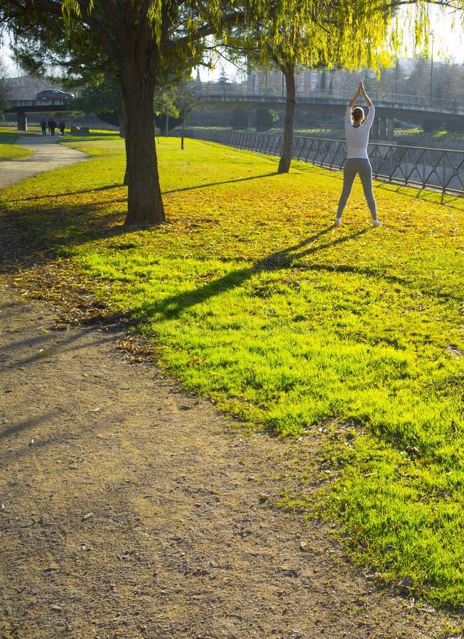 做伸展运动的妇女在秋天季节的都市公园 图库摄影