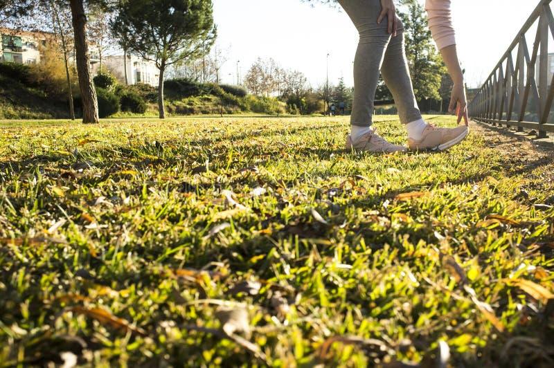 做伸展运动的妇女在秋天季节的都市公园 库存照片