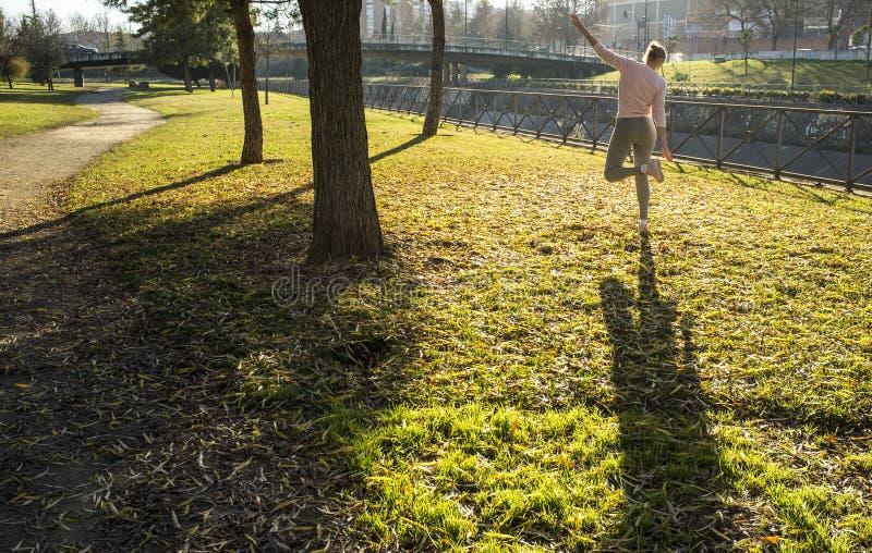 做伸展运动的妇女在秋天季节的都市公园 免版税库存图片