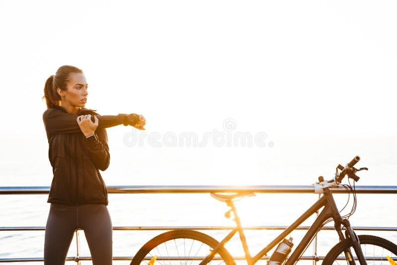 做伸展运动的运动的妇女照片,当站立在自行车附近户外在海洋时的日出期间 库存图片