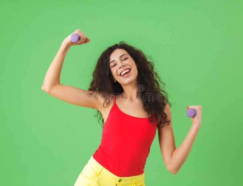 做体育和练习举重的白种人女孩画象对绿色墙壁 免版税图库摄影