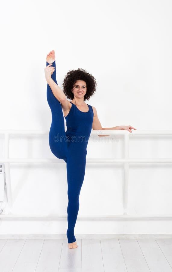 做体育的妇女舒展健身锻炼在体育健身房 免版税库存照片