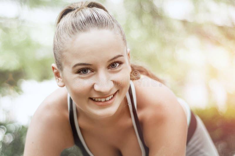 做体育的适合和运动的女孩在公园 健身体育woma 免版税库存图片