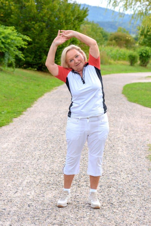 做体育锻炼的运动的年长妇女 免版税图库摄影