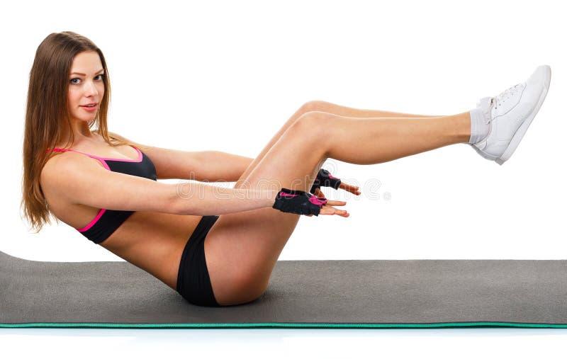 做体育锻炼的愉快的运动妇女,隔绝在白色 免版税库存照片