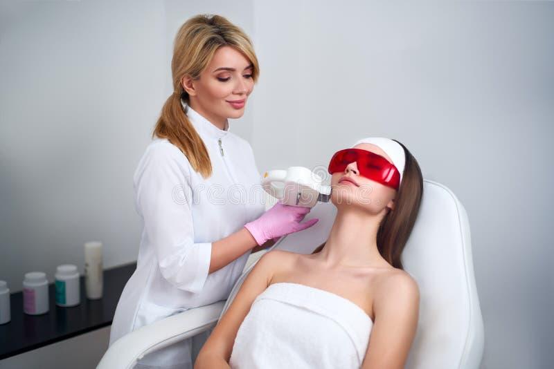 做俏丽的年轻女人面孔的美容师医生激光RF回复在发廊 Elos epilation头发撤除 免版税库存照片