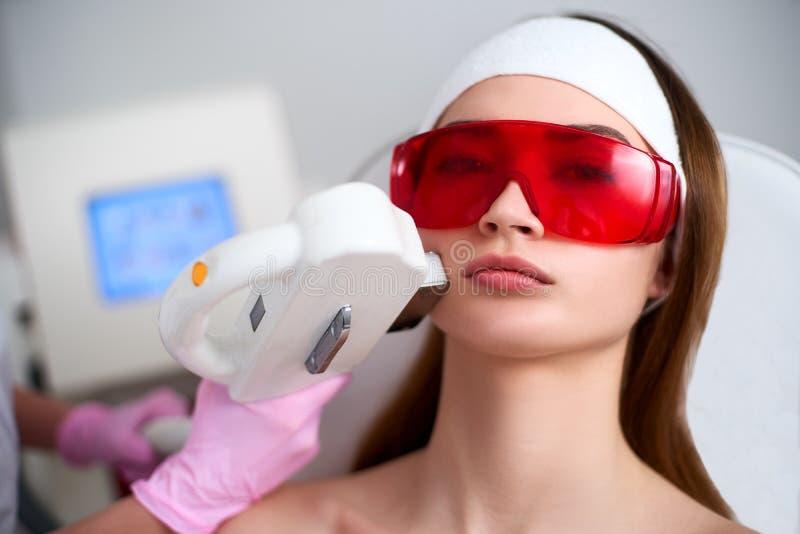 做俏丽的年轻女人面孔的美容师医生激光RF回复在发廊 Elos epilation头发撤除 库存图片