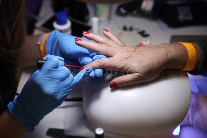 做修指甲并且绘钉子红色对妇女大师的手 图库摄影