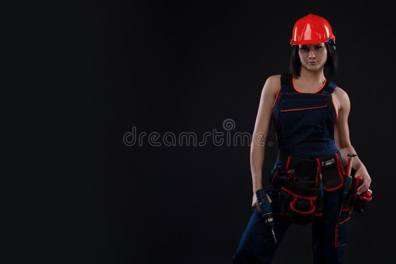 做修理的可爱的少妇在黑背景 一名女性建筑工人的画象 大厦,修理概念 复制 免版税库存图片