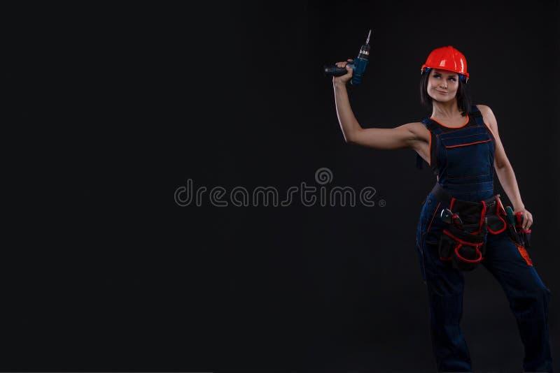 做修理的可爱的少妇在黑背景 一名女性建筑工人的画象 大厦,修理概念 复制 免版税库存照片