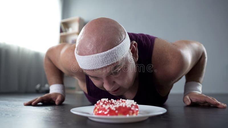 做俯卧撑和看在他前面的运动服的肥胖人鲜美多福饼 免版税图库摄影