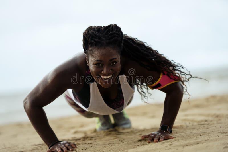 做俯卧撑外面在海滩的俯卧撑健身非洲妇女 免版税库存照片
