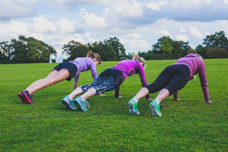 做俯卧撑的三名妇女在公园 免版税库存照片