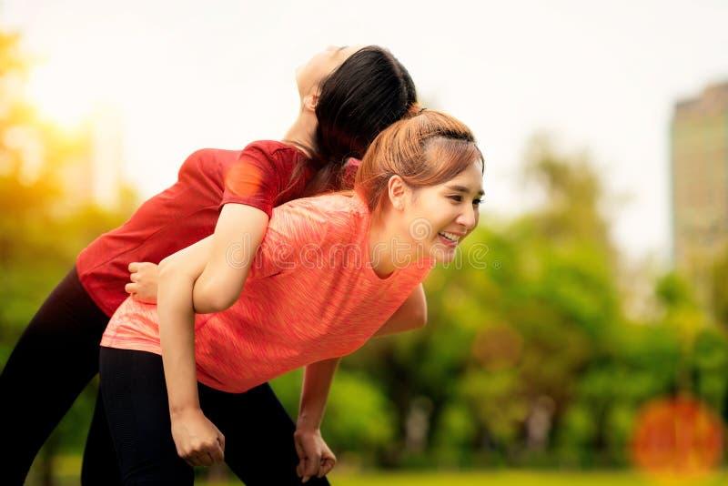 做俯卧撑的健身亚裔妇女在室外交叉训练锻炼期间 免版税库存图片