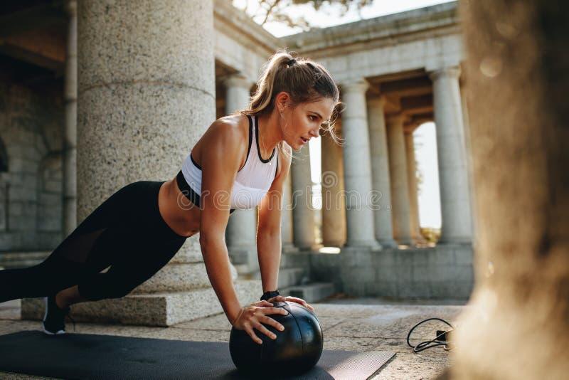 做俯卧撑的健身妇女使用药丸 免版税库存照片