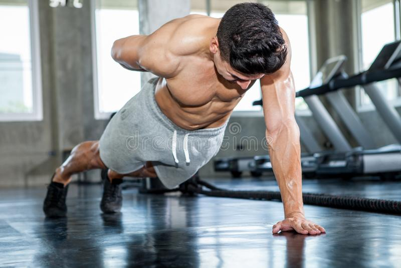 做俯卧撑的肌肉爱好健美者人行使单手在健身健身房的 赤裸上身的年轻体育人训练 解决 免版税库存图片