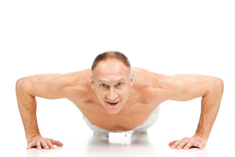 做俯卧撑的英俊的肌肉人 库存图片