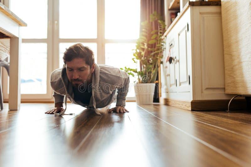 做俯卧撑的运动服的年轻人在他的客厅 免版税图库摄影