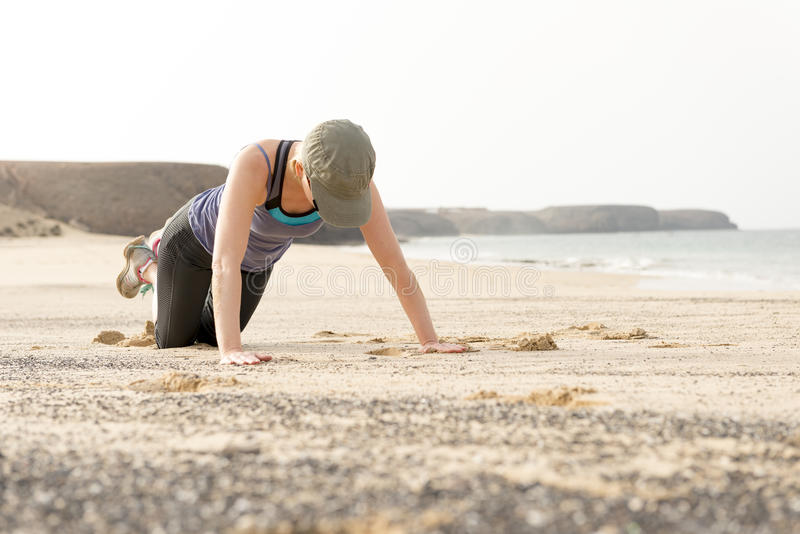 做俯卧撑的适合的妇女由海滩 免版税图库摄影