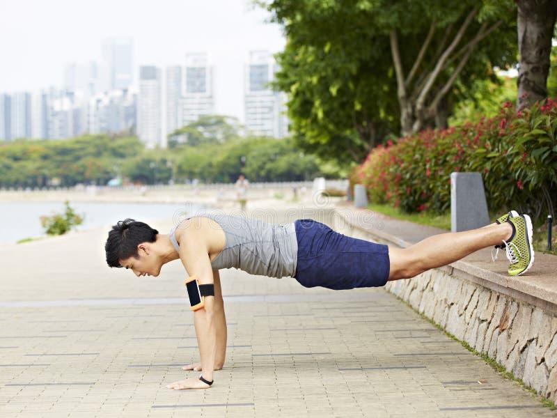 做俯卧撑的年轻亚裔人在公园 免版税库存照片