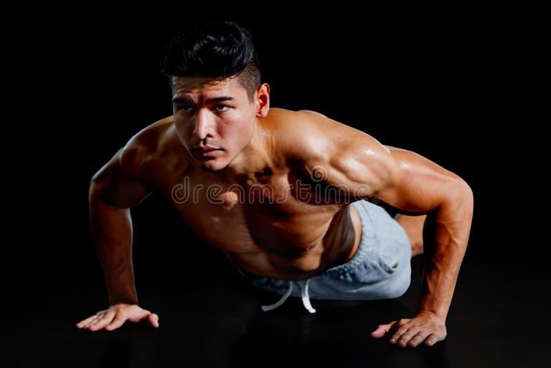 做俯卧撑锻炼的肌肉爱好健美者人隔绝在与裁减路线的黑背景 赤裸上身的健身年轻体育 库存照片