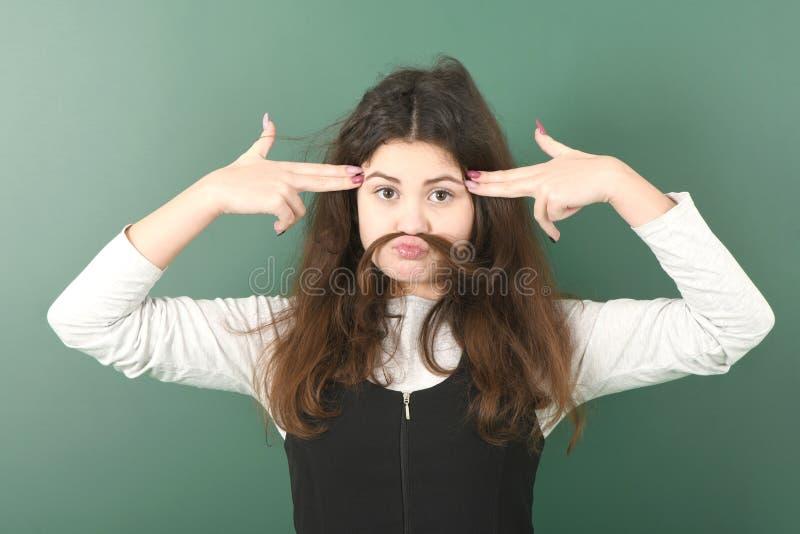 做假装髭的年轻嬉戏的女孩使用她自己的头发 图库摄影