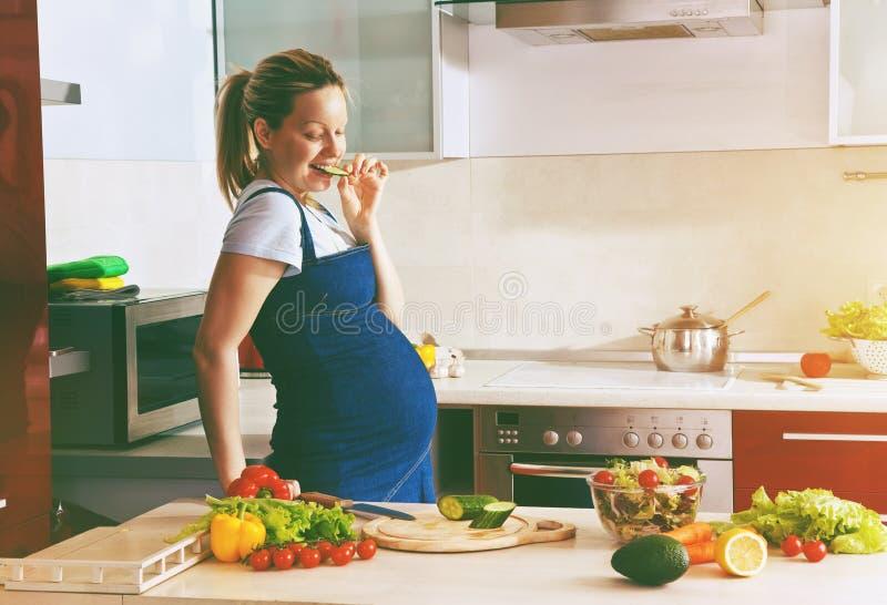 做健康沙拉的厨房的孕妇 库存照片