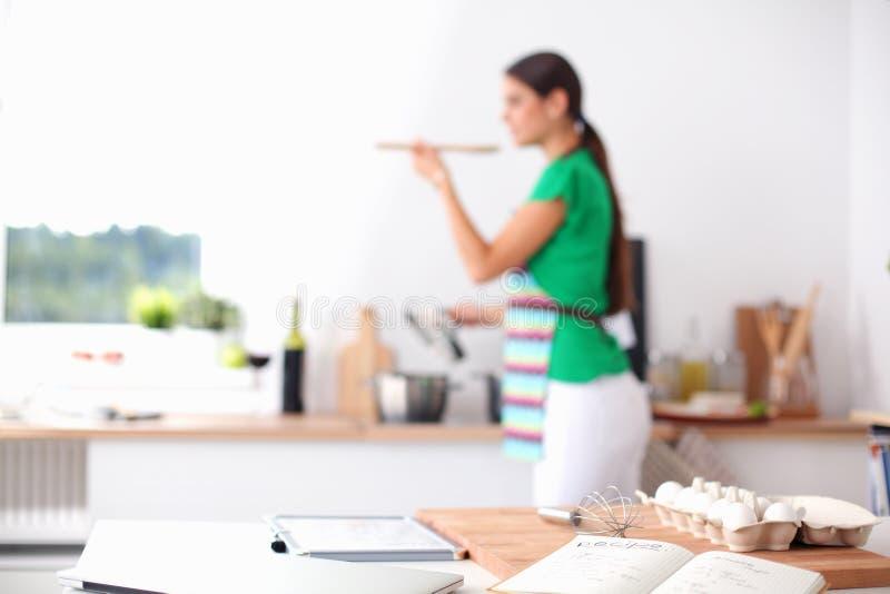 做健康食物的妇女站立微笑在厨房里 免版税库存照片