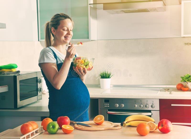 做健康水果沙拉的孕妇 库存照片