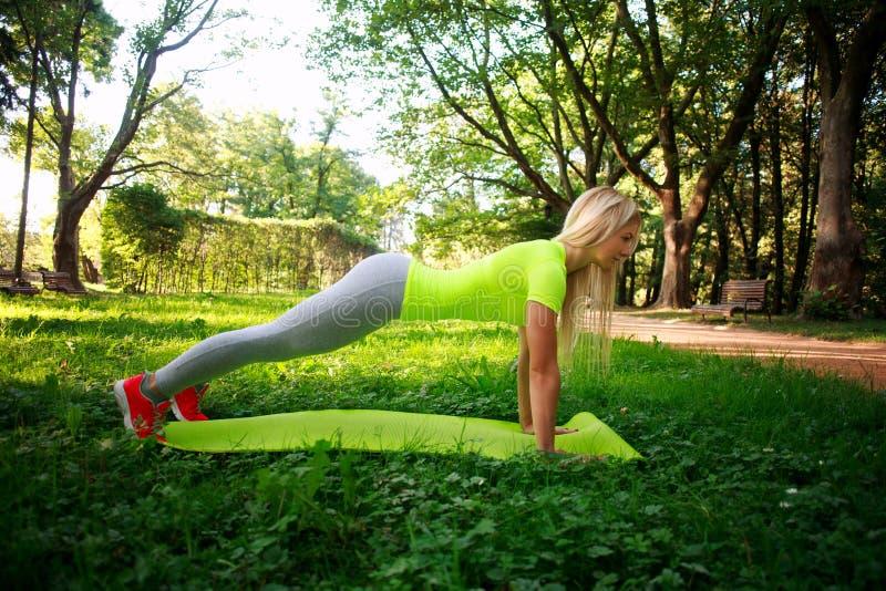 做健身俯卧撑的年轻运动的妇女在绿色城市公园 免版税库存照片