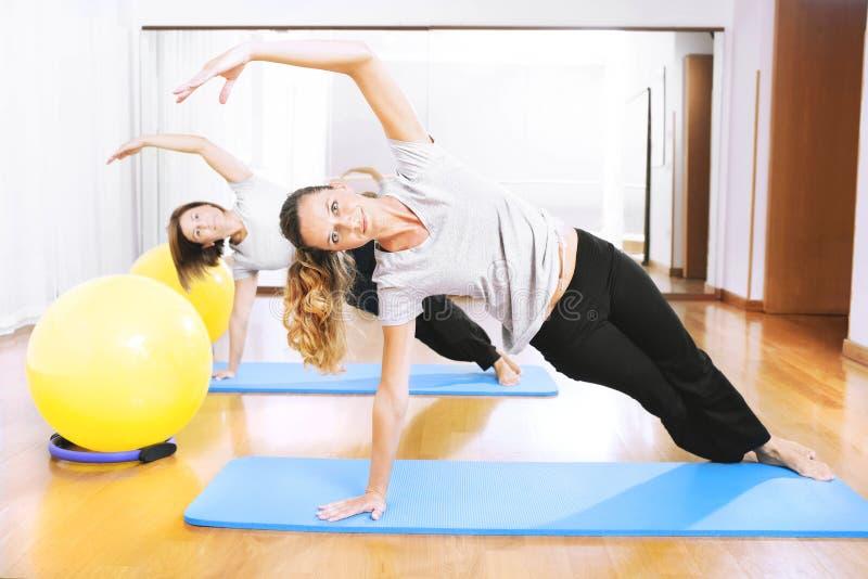 做健身的两名妇女在同步exercisen 图库摄影