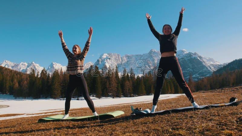 做健身的两年轻女人户外-站立用他们的手-森林和山在背景 库存照片