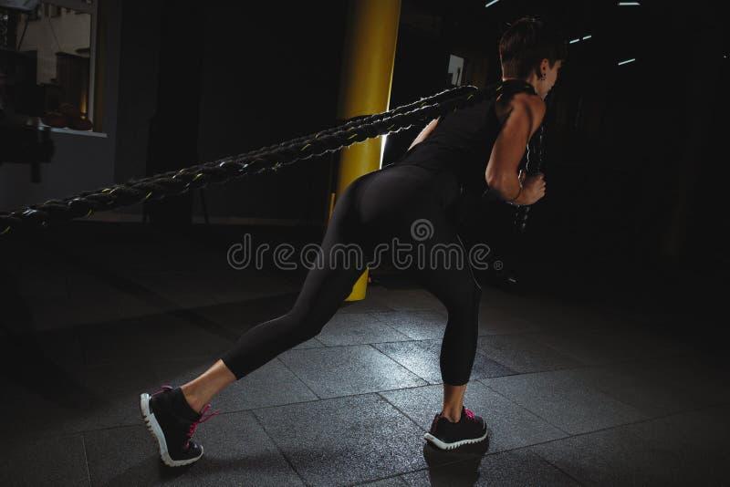 做健身的健身女孩在与大绳索的健身房行使在dar 免版税库存照片