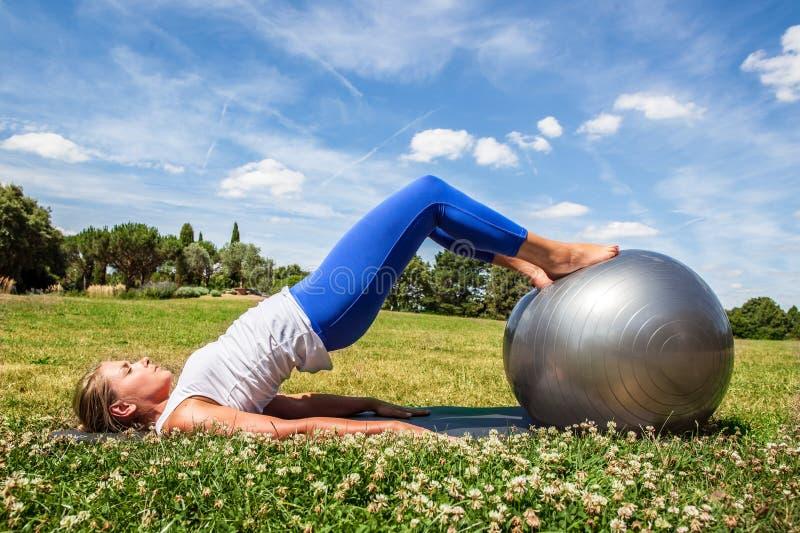 做健身的年轻白肤金发的妇女,定调子胃 库存照片