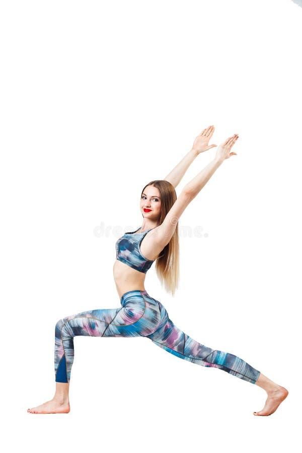 做健身锻炼的年轻白肤金发的妇女,隔绝在白色背景 免版税库存图片