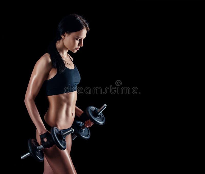 做健身锻炼的运动少妇反对黑背景 加大可爱的健身的女孩干涉与哑铃 免版税图库摄影