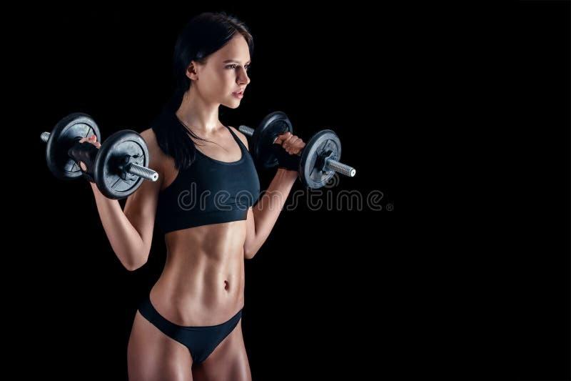 做健身锻炼的运动少妇反对黑背景 加大可爱的健身的女孩干涉与哑铃 免版税库存照片